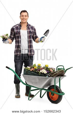 Full length portrait of a male gardener standing behind a wheelbarrow and holding a flower in a pot and a spade isolated on white background