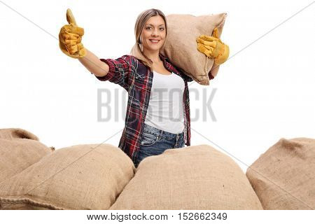 Female agricultural worker holding a burlap sack and giving a thumb up isolated on white background