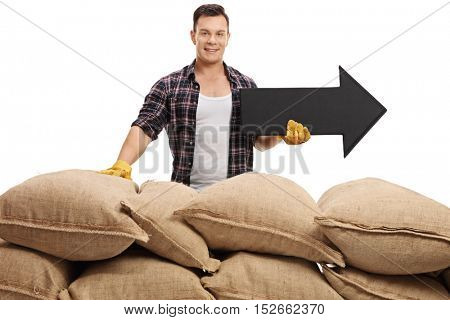 Male farmer posing behind a pile of burlap sacks with an arrow pointing right isolated on white background
