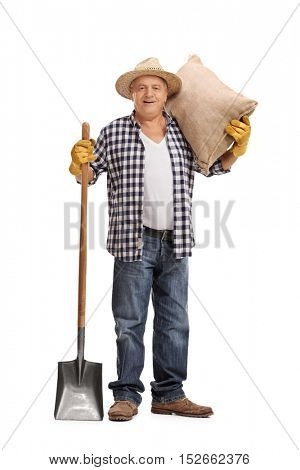 Full length portrait of a senior farmer posing with a burlap sack and a shovel isolated on white background