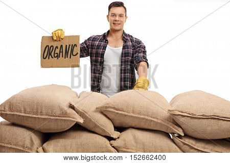 Young farmer standing behind a pile of burlap sacks and holding a cardboard sign that says organic isolated on white background