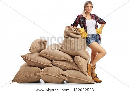 Cheerful female farmer leaning on a pile of burlap sacks isolated on white background