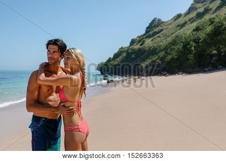 Portrait of beautiful young couple standing together on the beach and looking away. Woman in bikini and man in swim shorts on the sea shore on a summer day.