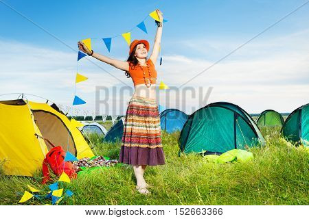 Portrait of happy girl, holding garland with yellow and blue flags, standing next to the tent at campsite