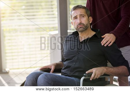handsome man in wheelchair with an assistant looking sad