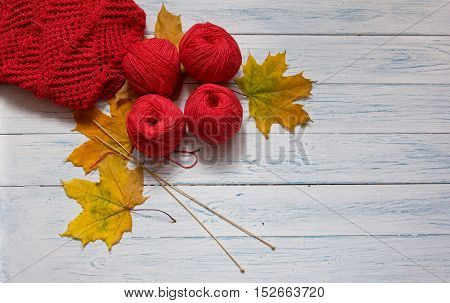Red yarn wooden knitting needles openwork knitting and yellow leaves are on white vintage wooden desk with place for your text. Top view.