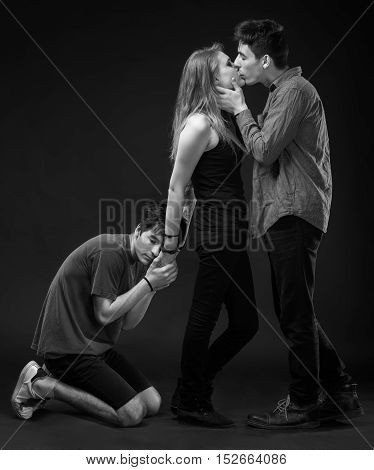 Love Triangle. Young Woman Posing With Two Young Man