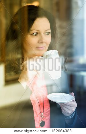 beautiful brunette woman standing by window and drinking coffee