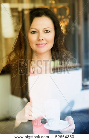 beautiful brunette woman standing by window with cup of coffee