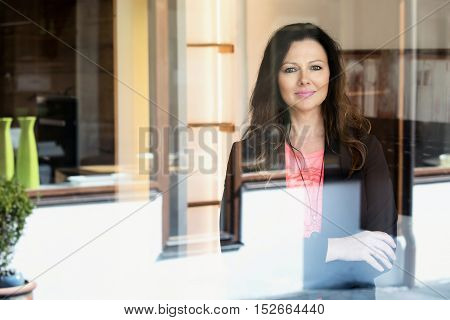 portrait of beautiful brunette woman smiling through window at camera