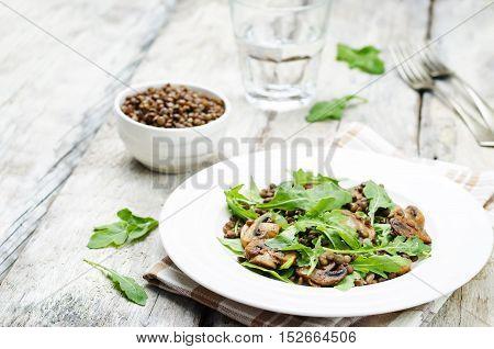 Green lentils mushroom arugula salad on wood background