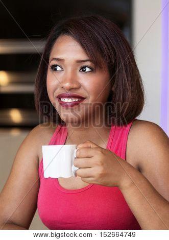 beautiful hispanic woman sitting at table and drinking coffee