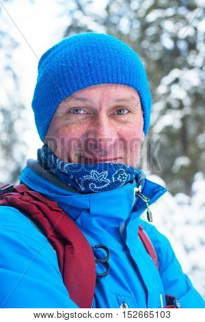 Portrait of smiling hiker in the winter forest.