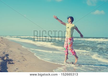 Sporty woman jumping and having fun on the beach in windy weather. Toned image.