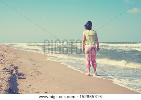 Woman is walking along the beach and looking at the stormy sea. Back view. Toned image.