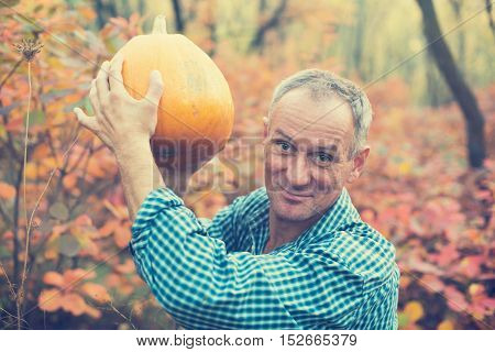 Man with pumpkin in hands enjoying life in the autumn park. Toned image.