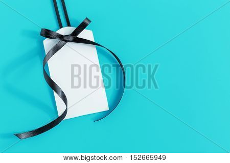 Tag with black ribbon on blue background