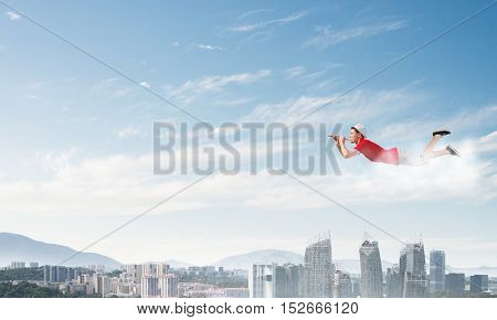 Young cheerful man flying high above city and playing fife