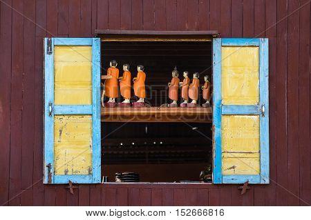 Traditional handicraft monk wooden doll in old window Myanmar