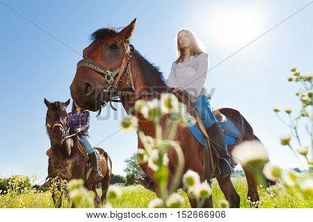 Portrait of two active young women training riding horses at sunny day