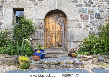 Rustic French gite doorway and window decorated with plants in Brittany France