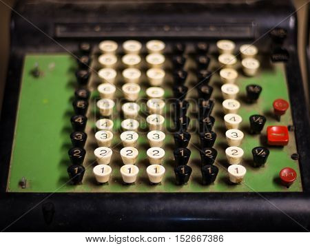 Old-fashioned manual cash register with black, white and red keys, a green background and black trim
