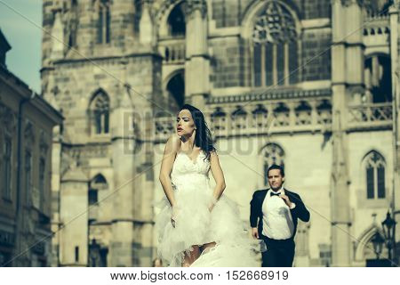 young wedding couple of sexy girl with brunette hair and red lips on pretty face in white bride dress and handsome man in black groom suit near castle or palace building sunny outdoor