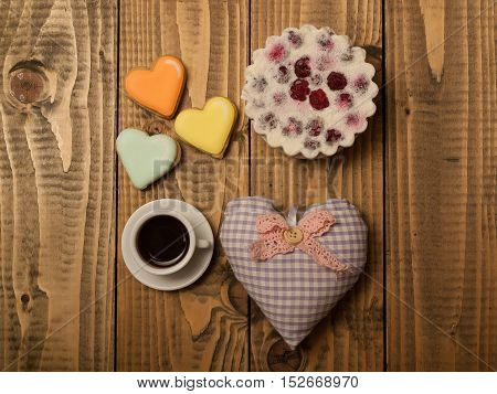 Tasty biscuit with berries colorful cookies cup of aromatic coffee drink on white saucer and decorative fabric heart pillow on wooden background
