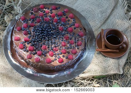 Chocolate cake dessert with fresh berries sweet blueberry and red raspberry on metallic plate and brown cup and saucer with coffee and aromatic pipes of cinnamon on sackcloth background