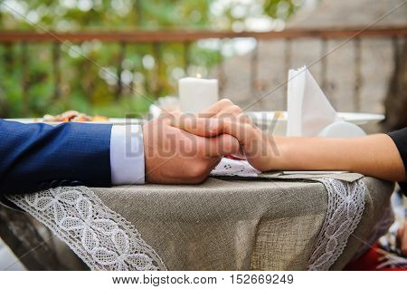 A loving couple holding hands. Young couple outdoor in cafe. Hands close up.