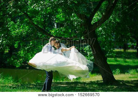 Handsome groom man circling with beautiful bride woman in wedding veil in hair and white flying dress on hands outdoors in summer park