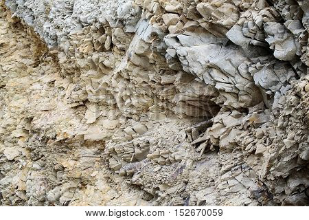 Grey rock or sharp stone formations minerals solid layer wall on sea coast beach on natural background