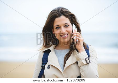 Woman Making Cellphone Call On Winter Trip To The Beach