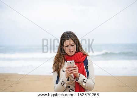 Nervous Woman Texting On Smartphone At The Beach On Autumn