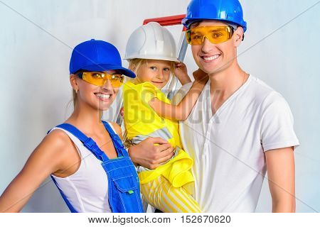 Young family with a kid moving into a new home and is preparing to repair apartments. Repair, construction and mortgage concept.