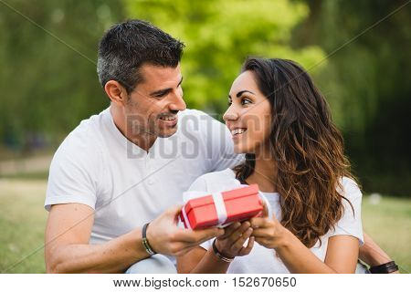 Loving couple celebrating birthday or anniversary with a present.