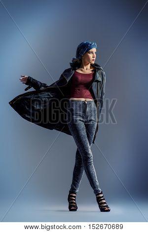 Studio fashion shot. Beautiful female model posing at studio in motion.