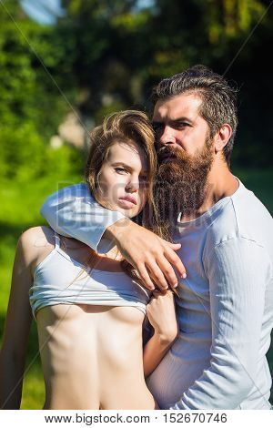 young couple of sexy woman with long blonde hair and bare belly with bearded handsome man with beard and stylish hairstyle standing in lawn with green grass sunny summer outdoor