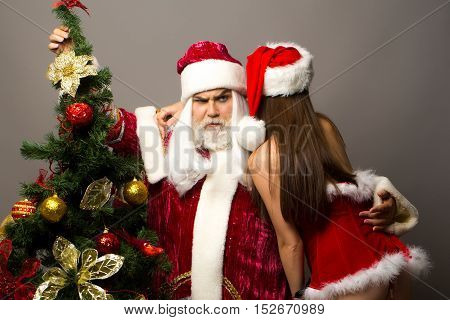 Severe santa claus man with white beard in new year red suit listens to whisper of pretty girl in sexy dress