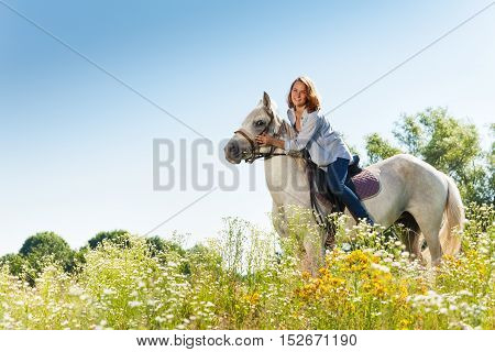 Side view portrait of beautiful woman hugging white horse in summer field