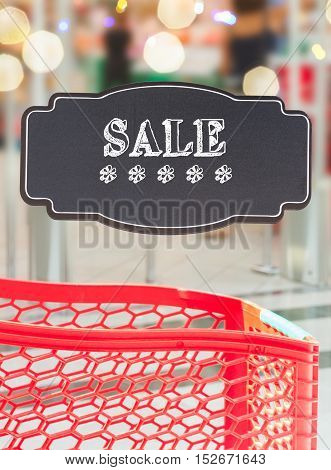 red cart supermarket store with sale text on black lable