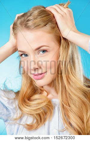 Cute young woman with beautiful blonde hair posing with positive emotions. Light summer mood. Studio shot.