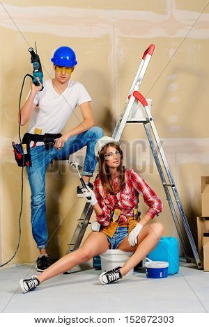 Male and female construction workers. Smiling young couple in love is going to renovate their new apartment.