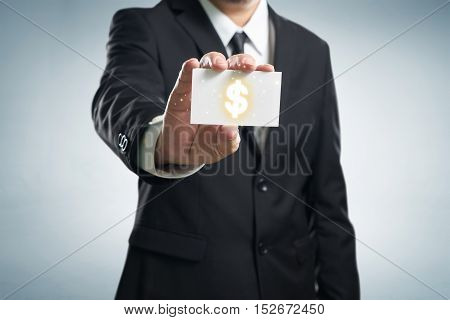 Dollar sign. Businessman in suit shows business card.