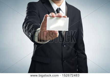 businessman in suit holding name card with dollar symbol