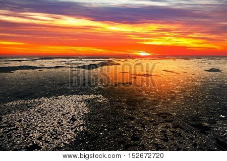 Sunset on a sea in winter scenery.