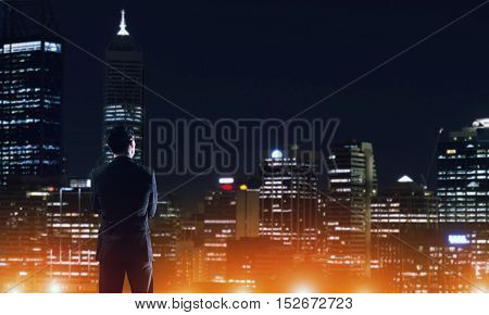 Elegant businessman looking at night city