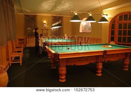 Kiev Ukraine - November 12 2006: Billiard interior in billiard club woman with kids playing in the pool background