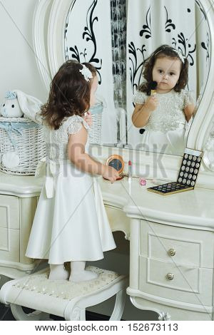 Cute girl with cosmetic brush. Cute baby plays with make up