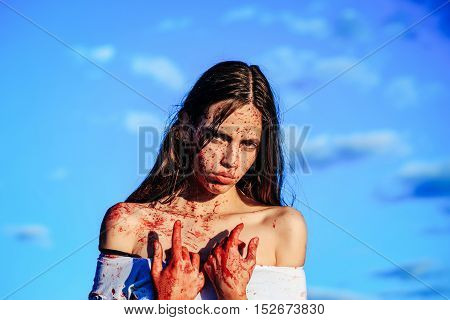 Halloween zombie girl or pretty young woman with bloody brunette hair with wounds and red blood outdoors on blue sky